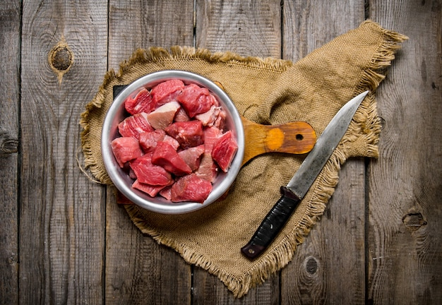 Cięcie surowego mięsa dużym nożem. na drewnianym stole.