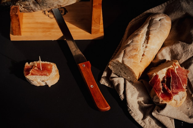 Cięcie szynki iberyjskiej chlebem, drewnem, nożem.