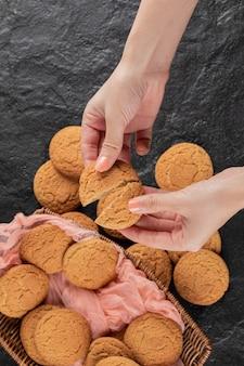 Cięcie w dłoni ciasteczka owsianego na dwie części.