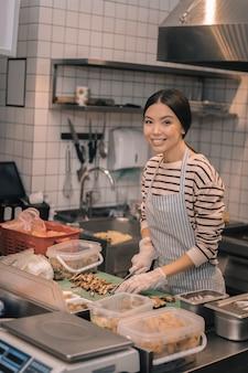 Cięcie w kuchni. ciemnowłosy pomocny pracownik restauracji w rękawiczkach podczas cięcia w kuchni