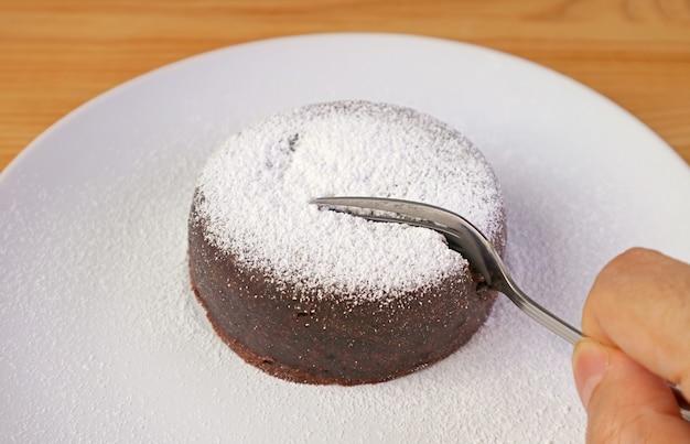 Cięcie widelcem na pyszne, bogate ciasto czekoladowe posypane cukrem pudrem