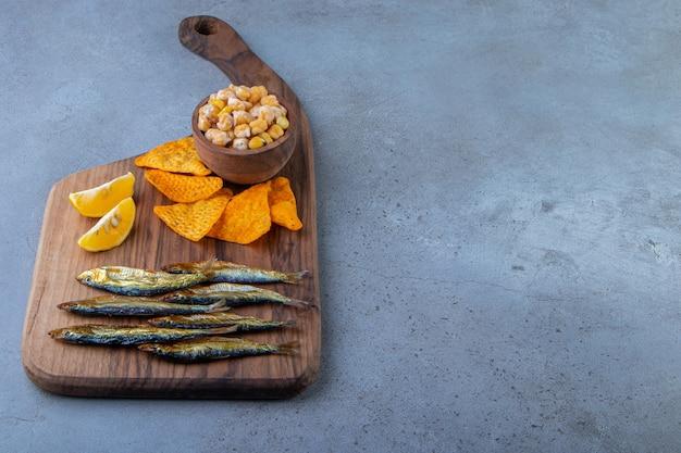 Ciecierzyca, plasterki cytryny, chipsy i suszone szproty na desce do krojenia, na niebieskim tle.
