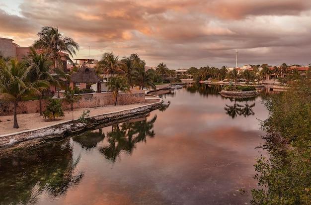 Ciek wodny w środku dzielnicy mieszkalnej puerto aventuras w meksyku w pomarańczowej godzinie.