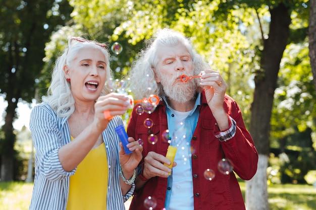 Ciekawa aktywność. miła szczęśliwa para stojąc razem podczas dmuchania baniek mydlanych