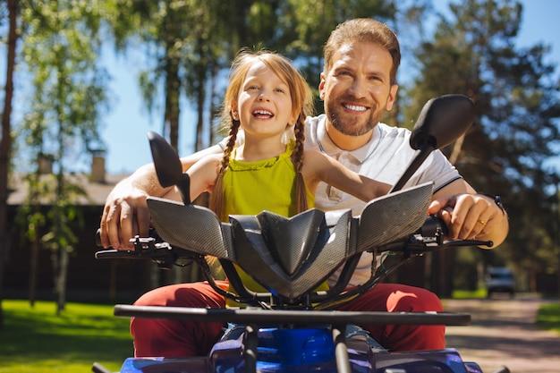 Ciekawa aktywność. zaalarmowana urocza dziewczyna uśmiechnięta i prowadząca atv ze swoim tatą