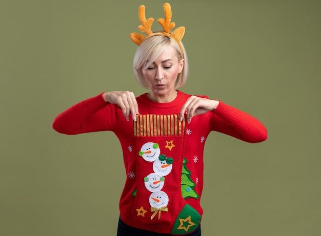Ciekawa blondynka w średnim wieku ubrana w świąteczną opaskę z poroża renifera i świąteczny sweter trzyma i patrzy w świąteczne skarpety odizolowane na oliwkowej ścianie