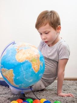 Ciekawa chłopiec patrzeje na ziemskiej kuli ziemskiej