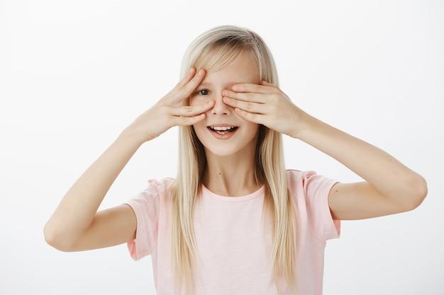 Ciekawa córka chce zobaczyć, co ojciec przygotował na urodziny. portret zaintrygowanej, niecierpliwej uroczej dziewczyny o pięknych blond włosach, zakrywającej oczy dłońmi i zerkającej z szerokim uśmiechem na szarą ścianę