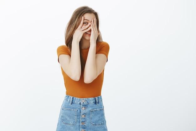 Ciekawa dziewczyna zaglądająca przez palce, chce się dowiedzieć, co się dzieje