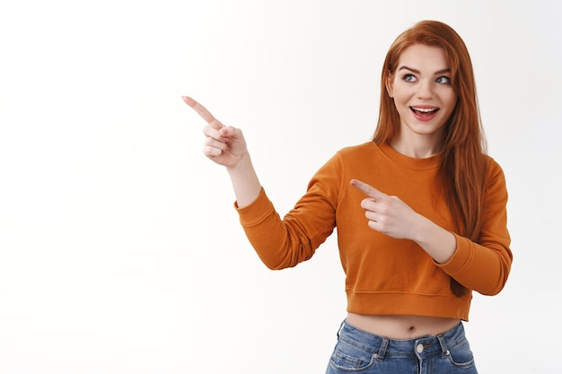 Ciekawa entuzjastyczna przystojna ruda europejska kobieta podekscytowana uśmiechnięta szeroko spojrzenie wskazująca zaintrygowana lewa strona kopia przestrzeń zainteresowana niesamowita zupełnie nowa reklama produktu, biała ściana