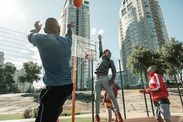 Ciekawa gra. przyjemny młody człowiek trzymający rękę, próbując dosięgnąć piłki