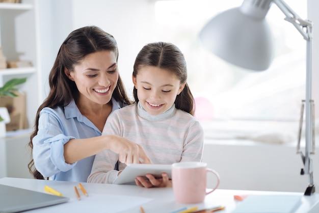 Ciekawa historia. ładny pozytywny miła dziewczyna uśmiecha się i czyta książkę, siedząc razem z matką
