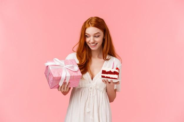 Ciekawa i wesoła, wesoła ruda kobieta w białej sukni, świętująca urodziny