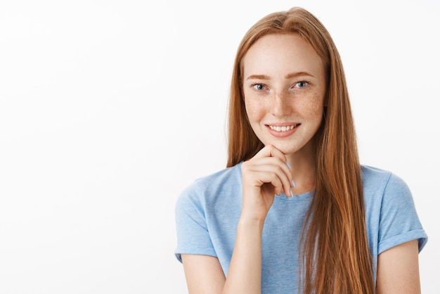 Ciekawa i zainteresowana atrakcyjna rudowłosa modelka z uroczymi piegami uśmiechająca się radośnie podczas słuchania ciekawej historii trzymającej rękę na brodzie wyrażającej intrygę i radość na szarej ścianie