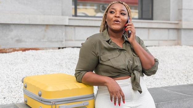 Ciekawa kobieta rozmawia przez telefon obok swojego żółtego bagażu