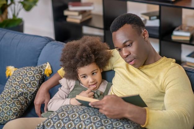 Ciekawa książka. ciemnoskóry młody dorosły troskliwy tata czytający książkę małej zainteresowanej córce siedzącej razem na wygodnej kanapie