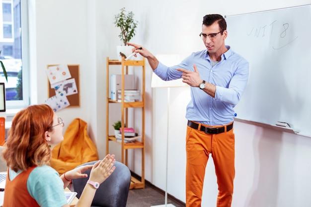 Ciekawa lekcja. inteligentna, utalentowana nauczycielka stojąca przed swoją uczennicą i wyjaśniająca jej nowy materiał