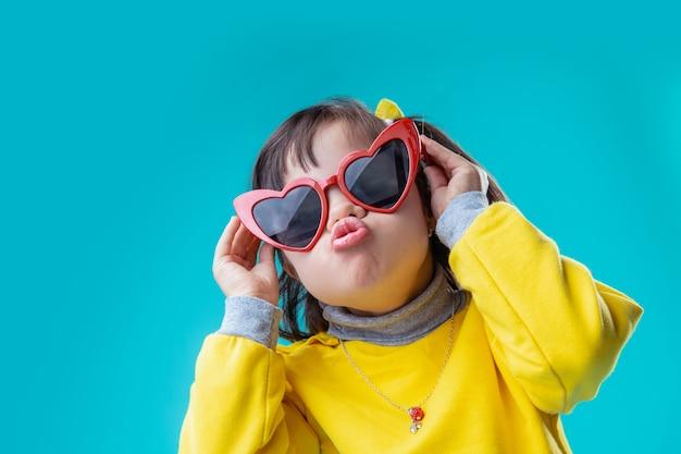 Ciekawa mała dama. pozytywnie zainteresowana dziewczyna w dziwnych okularach w kształcie serca i wypychająca usta