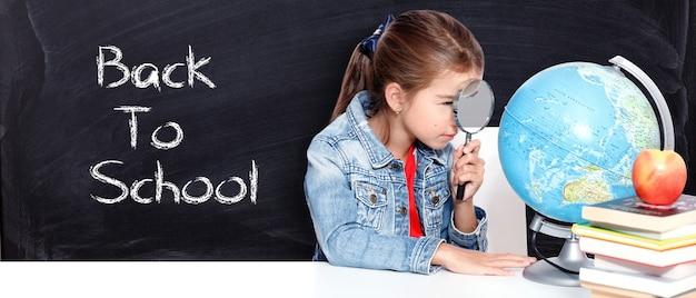 Ciekawa mała dziewczynka patrząca przez szkło powiększające na świecie