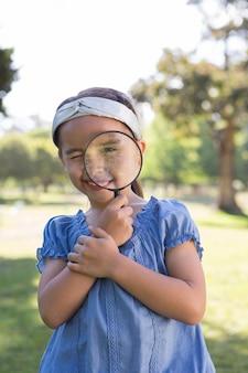 Ciekawa mała dziewczynka patrzeje przez powiększać - szkło