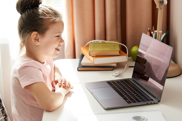 Ciekawa mała dziewczynka używa laptop przy biurkiem