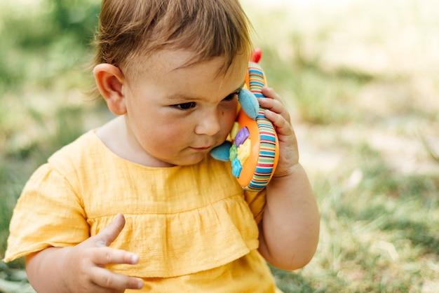 Ciekawa mała dziewczynka używa zabawkarskiego telefon outdoors w letnim dniu