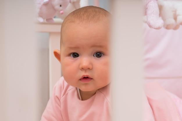 Ciekawa mała dziewczynka zaglądająca dookoła jej łóżeczka na aparat z zamyślonym wyrazem twarzy z bliska