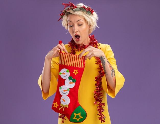 Ciekawa młoda blondynka ubrana w świąteczny wieniec na głowę i świecącą girlandę na szyi, trzymając świąteczną skarpetę, patrząc w nią na białym tle na fioletowej ścianie z miejscem na kopię