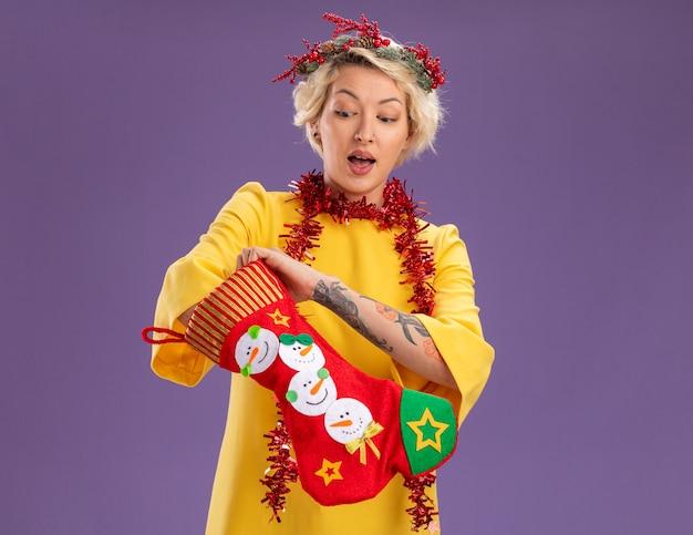 Ciekawa młoda blondynka ubrana w świąteczny wieniec na głowę i świecącą girlandę na szyi, trzymając świąteczną skarpetę, wkładając dłoń do środka, patrząc na nią na białym tle na fioletowej ścianie z miejscem na kopię