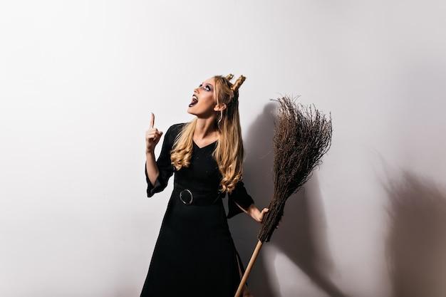 Ciekawa młoda czarownica patrząc w górę. ładny żeński czarodziej z miotłą stwarzających w halloween