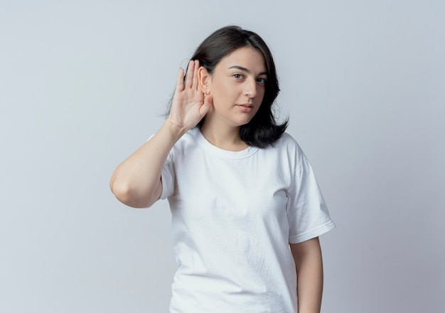 Ciekawa młoda dziewczyna całkiem kaukaski robi nie słyszy gestu na aparat na białym tle na białym tle z miejsca na kopię