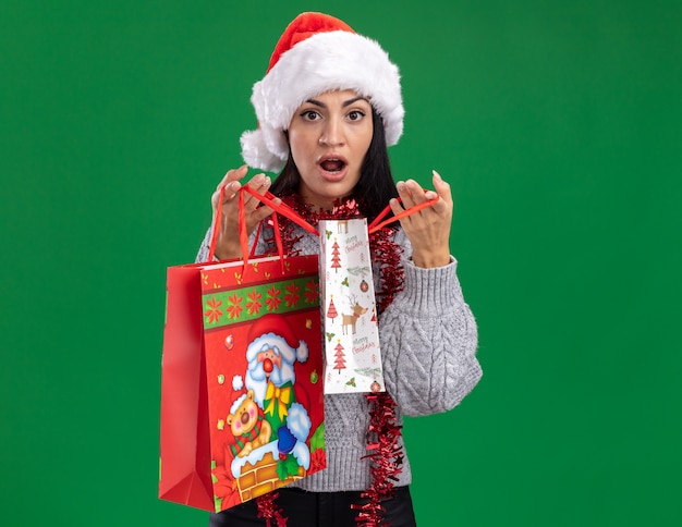 Ciekawa młoda kaukaska dziewczyna ubrana w świąteczny kapelusz i świecącą girlandę na szyi, trzymając torby na prezenty świąteczne, otwierając jedną na zielonej ścianie z miejscem na kopię