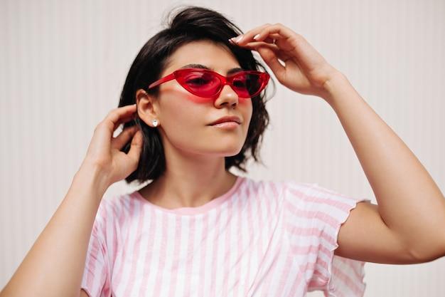 Ciekawa młoda kobieta szuka drogi na białym tle na teksturowanej tle. atrakcyjna kaukaska kobieta w letnim stroju pozuje w okularach przeciwsłonecznych.