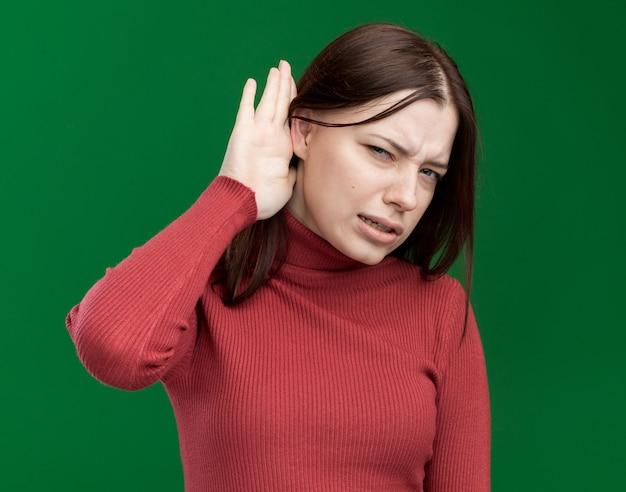 Ciekawa młoda ładna dziewczyna robi, że nie słyszę twojego gestu na zielonej ścianie