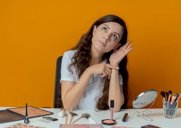 Ciekawa młoda ładna dziewczyna siedzi przy stole do makijażu z narzędziami do makijażu robi nie słyszy gestu i patrząc w górę na białym tle na pomarańczowym tle