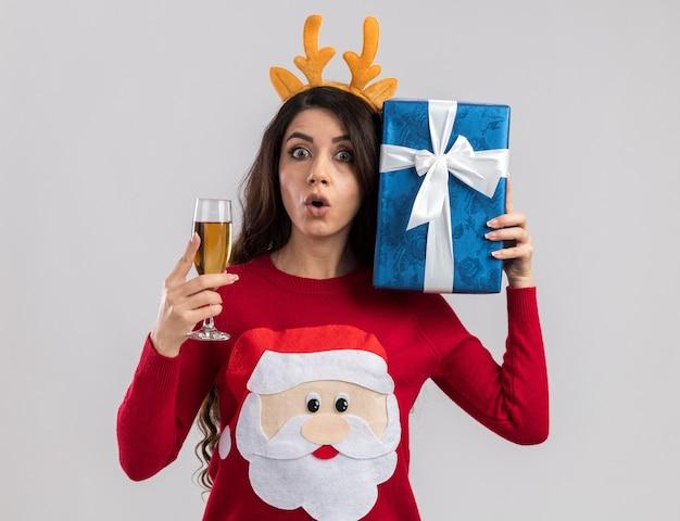 Ciekawa młoda ładna dziewczyna ubrana w opaskę z poroża renifera i sweter świętego mikołaja trzymająca kieliszek szampana i pakiet prezentów w pobliżu głowy patrząc