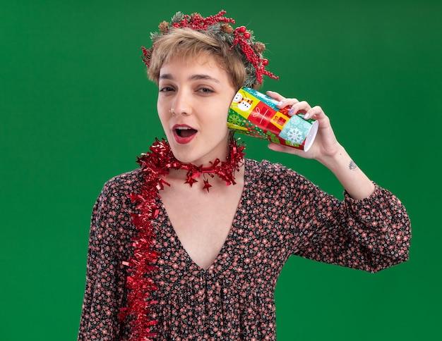 Ciekawa młoda ładna dziewczyna ubrana w świąteczny wieniec na głowę i świecącą girlandę na szyi, trzymając plastikowy świąteczny kubek obok ucha, słuchając tajemnic patrząc na kamerę na białym tle na zielonym tle