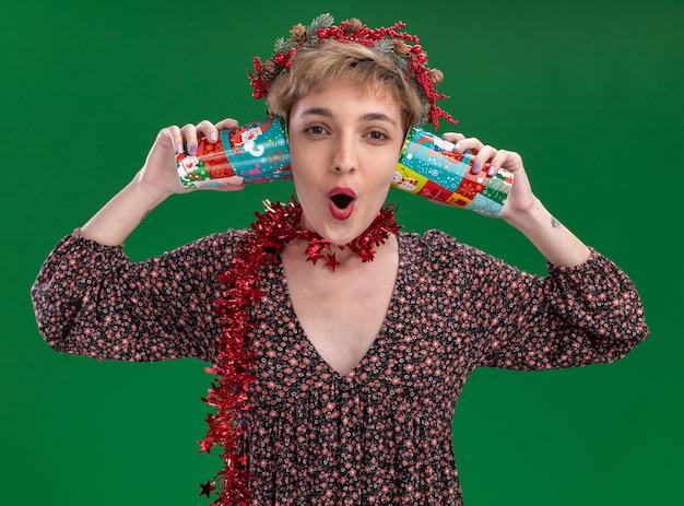 Ciekawa młoda ładna dziewczyna ubrana w świąteczny wieniec na głowę i świecącą girlandę na szyi trzymająca plastikowe kubki świąteczne obok uszu słuchająca sekretów patrząc na kamerę odizolowaną na zielonym tle