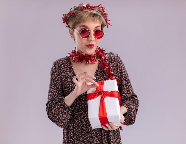 Ciekawa młoda ładna dziewczyna ubrana w świąteczny wieniec na głowę i świecącą girlandę wokół szyi w okularach trzyma pakiet prezentów chwytając wstążkę patrząc na kamery na białym tle