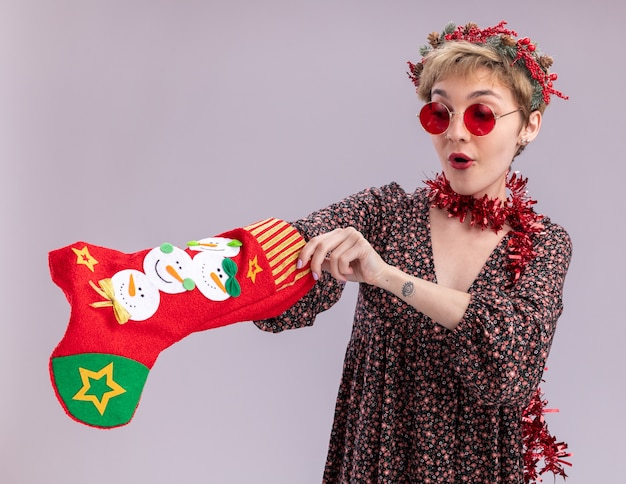 Ciekawa młoda ładna dziewczyna ubrana w świąteczny wieniec na głowę i świecącą girlandę wokół szyi w okularach trzyma świąteczną skarpetę patrząc na nią wkładając dłoń do środka na białym tle