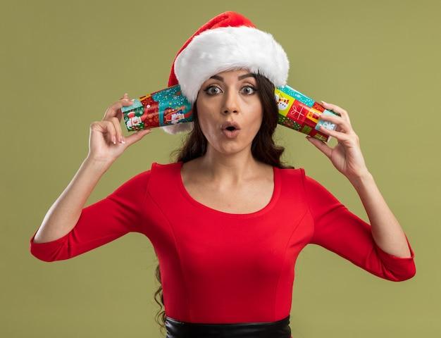 Ciekawa młoda ładna dziewczyna w kapeluszu santa trzymająca świąteczne filiżanki kawy obok uszu słuchając rozmów na białym tle na oliwnej ścianie