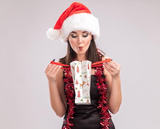 Ciekawa młoda ładna kaukaska dziewczyna nosi santa hat i blichtr wianek wokół szyi, trzymając worek prezentów świątecznych, patrząc wewnątrz, co sprawia, że twarz ryby na białym tle z miejsca kopiowania