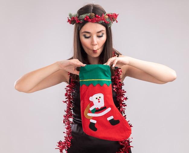 Ciekawa młoda ładna kaukaska dziewczyna nosi świąteczny wieniec głowy i blichtr wianek wokół szyi, trzymając i patrząc wewnątrz świątecznej pończochy, co rybą twarz na białym tle