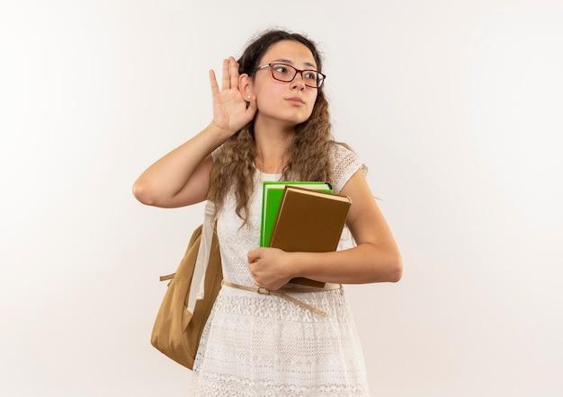 Ciekawa młoda ładna uczennica w okularach i plecak trzymając książki robi nie słyszy, jak gest patrząc na bok na białym tle na biały z miejsca na kopię