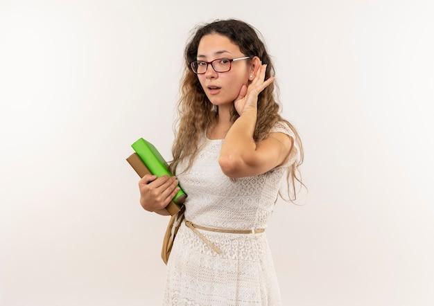 Ciekawa młoda ładna uczennica w okularach i torbie z książkami na plecach, która nie słyszy gestu na białym tle z miejsca na kopię