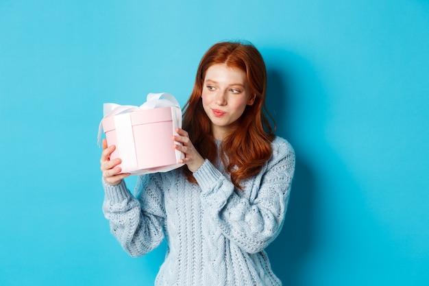 Ciekawa nastolatka z rudymi włosami, potrząsająca pudełkiem i zastanawiająca się, co w środku, stojąca na niebieskim tle.