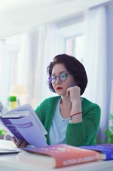Ciekawa nauka. miła inteligentna kobieta czytająca książkę o numerologii siedząc w swoim biurze
