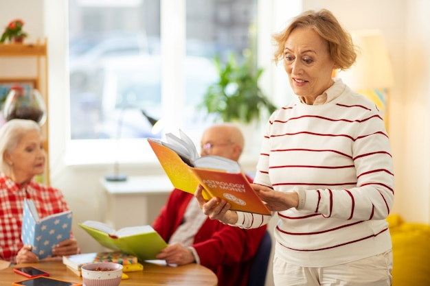 Ciekawa nauka. pozytywna starsza kobieta uśmiechająca się podczas czytania książki o astrologii