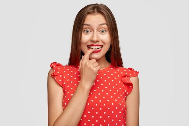 Ciekawa piękna kobieta z czerwoną szminką pozuje na białej ścianie