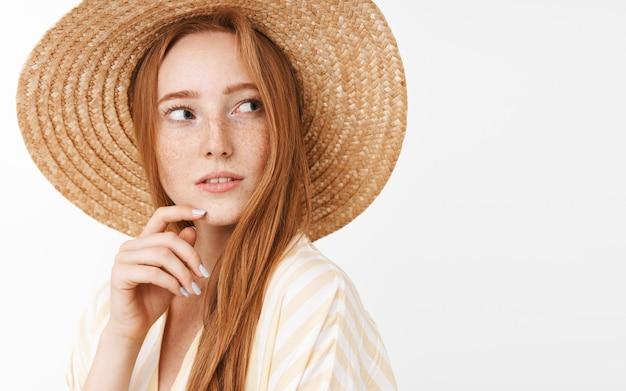 Ciekawa, przemyślana, urocza rudowłosa dziewczyna z uroczymi piegami w modnym letnim słomkowym kapeluszu skręca w prawo i patrzy z zainteresowaniem i zaintrygowanym spojrzeniem dotykając brody, myśląc i obserwując
